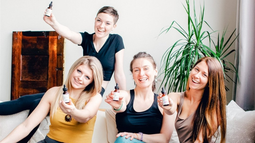 4 women holding CBD tinctures and smiling