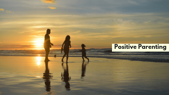 Positive Parenting title family frolicking on beach at sunset.