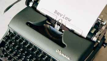 black and white typewriter on table saying review on the page