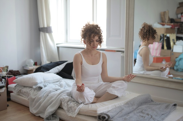 young woman sitting cross-legged on her bed practising self-care by meditating