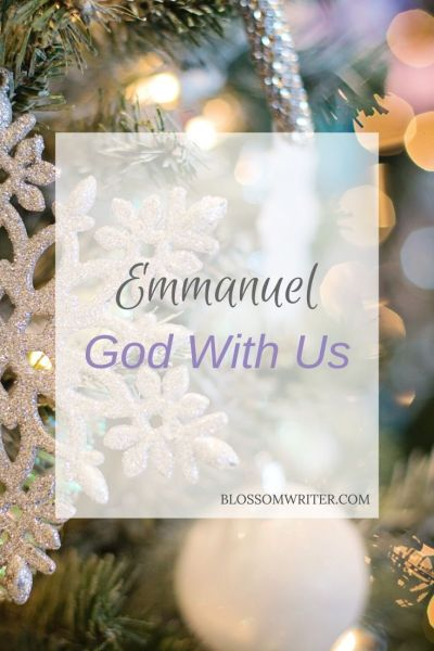 "A white snowflake ornament hanging on a Christmas tree. Text reads, ""Emmanuel God With Us."""