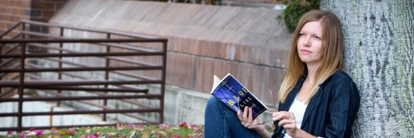 An image of Melissa leaning against a tree trunk reading Donald Miller's Blue Like Jazz.