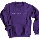 """But First, Kindness"" Sweatshirt shown in purple."
