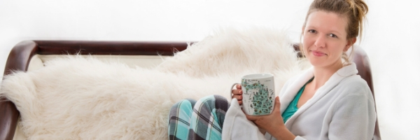 Melissa McMillan sitting on a couch in her pajamas, holding a mug of coffee.