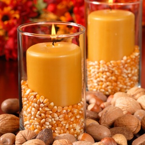 Candle in an autumn setting with corn and nuts