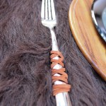 Leather Wrapped Silverware For A Rustic Outdoors Tablescape- See More Woodsy Tablescape Details On B. Lovely Events