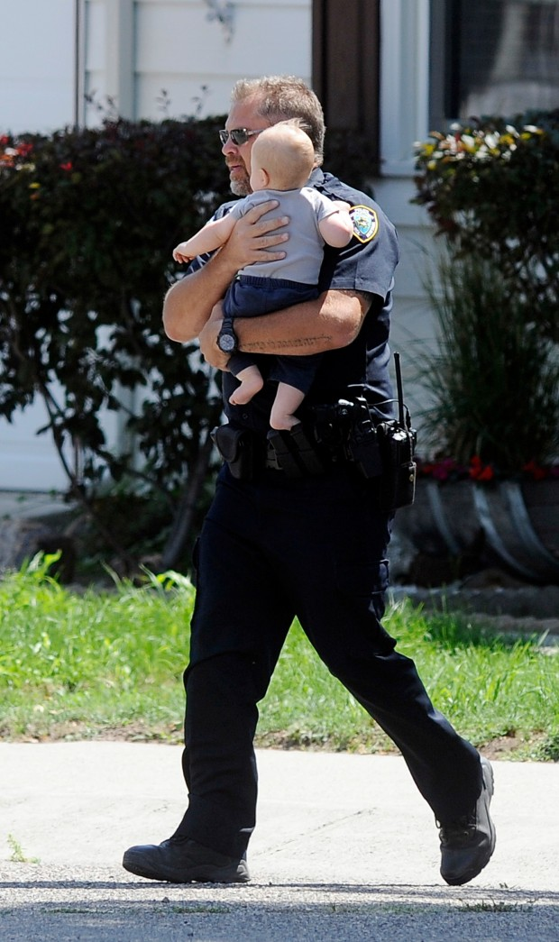 A Laurel police officer carries a child to safety