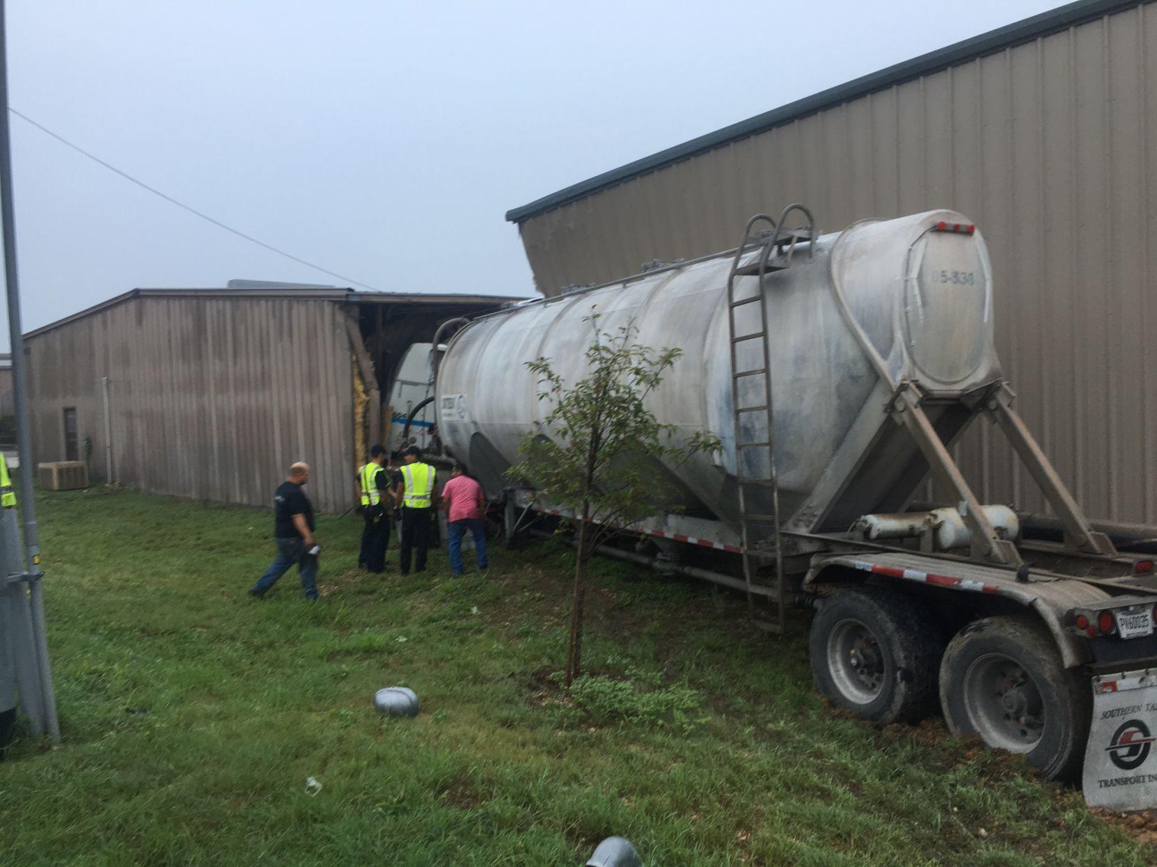 Tanker truck smacks buildings.