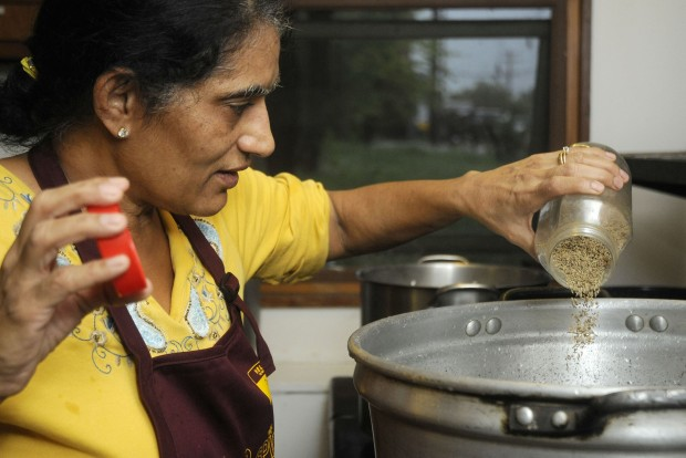 """Ranjeet Chhabra pours cumin seeds into a pot as she helps prepare for Sikh Feast, one of the weekly Rice and Spice meals at the Gaia House on Friday, August 31, 2012 in Carbondale. (Aaron Eisenhauer / The Southern)"" (source: The Southern Illinoisan)"