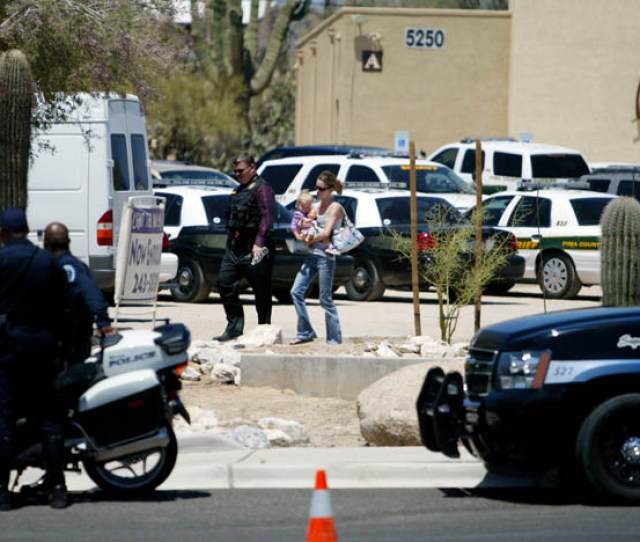 A Pima County Sheriffs Officer Escorts A Woman With Her Child In Front Of The Desert Son Community Church Tuesday Afternoon After A 60 Year Old Man