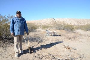 Manuel digs up the roots of a mesquite bush for firewood, about 100 yards from the border fence.