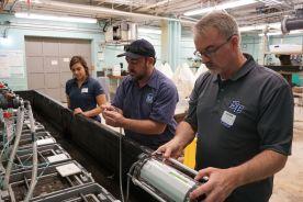 Gabriella Dipreta, Dave Veilleux, and Sean Grace collect data with a fluorometer during an ocean acidification experiment.