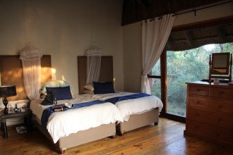 A bedroom with views across the lake and into the forest