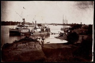 """October 2020 C: Untitled: River bank with ships moored. Steamship to left of print named """"Elizabeth"""". Three men on bareback horses near shore in foreground. Black man standing on shore in foreground. More ships and men along shore to right."""