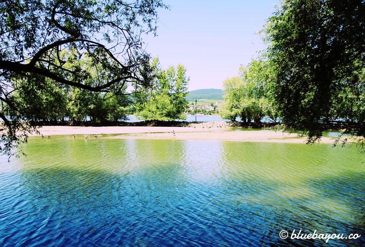 Schöne Farbspiele am Rhein vor kleinen Buchten, die zum Ausruhen einladen.
