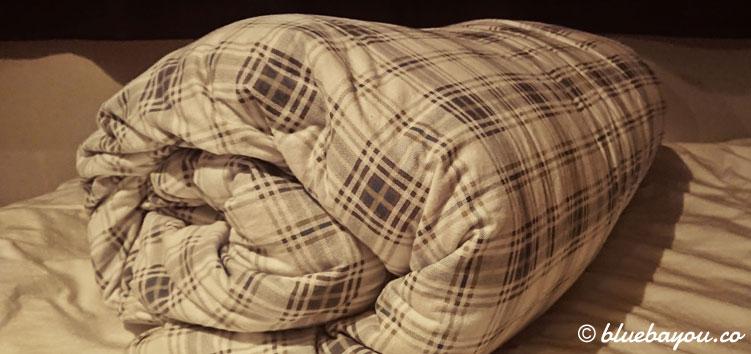 Eine gerollte Bettdecke verhindert, dass man seinen Kopf auf schmutzige Bereiche legen muss und spart tagsüber Platz.