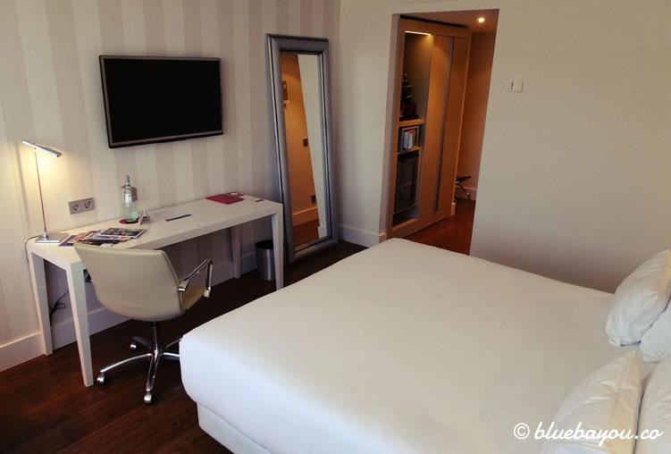 Blick auf das Bett und den Schreibtisch im NH Collection Hotel Köln Mediapark.