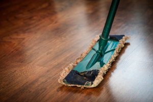 Green mop on a brown wooden floor