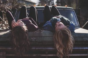 two girls lying on a car, making living with a roommate in Edison look easy