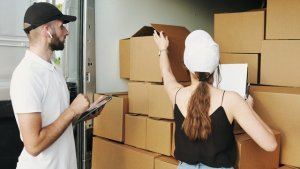 a woman helping movers with boxes