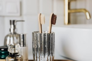 Two toothbrushes and a bottle of perfume in the bathroom, zoomed in