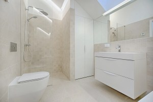 a bathroom with white cabinets, toilet, and shower
