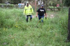 Tarkington firefighter Albert Crawford and Pct. 5 Constable David Hunter walk through knee-high grass as they check on residents of Sam Houston Lake Estates on Tuesday.