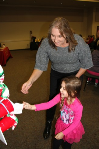 """Susan Giberson lets her granddaughter, McKenzie, pick the right cup in a """"Naughty or Nice"""" game at the Dayton Chamber luncheon on Dec. 4 at the Dayton Community Center."""