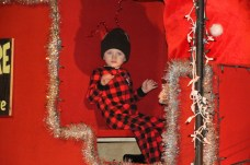 """A.J. Chambers, son of Andrew and Sherry Chambers, rode on a float featuring his dad dressed as """"The Grinch."""""""