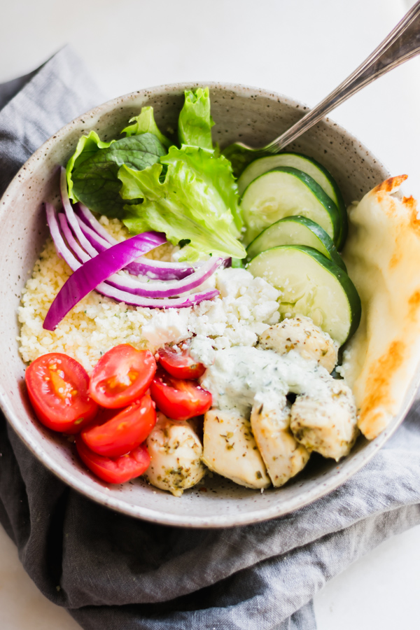 Chicken Gyro Bowls with Homemade Tzatziki Sauce - Bowls filled with lemon + herb marinated chicken, couscous, fresh greens, tomatoes, feta, red onions, and cucumber. Serve with naan bread and tzatziki sauce! You'll want to memorize this one! #gyros #chicken #chickengyros #bowlrecipes #healthyrecipes #healthyfood #chickenrecipe #mealprep #glutenfree | bluebowlrecipes.com