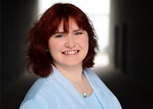 weibliche Person mit roten Haaren und blauer Bluse