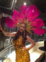 Showgirl in gold with pink feathers