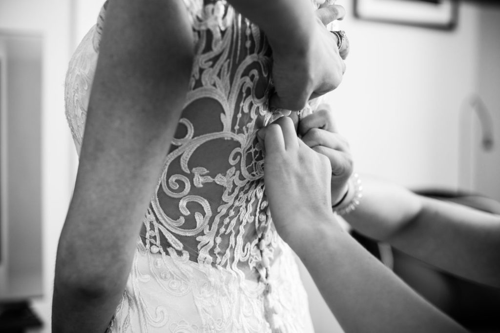 black and white image of lace back wedding dress being buttoned