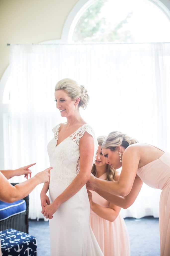 smiling bride as bridesmaids button up the back of her dress