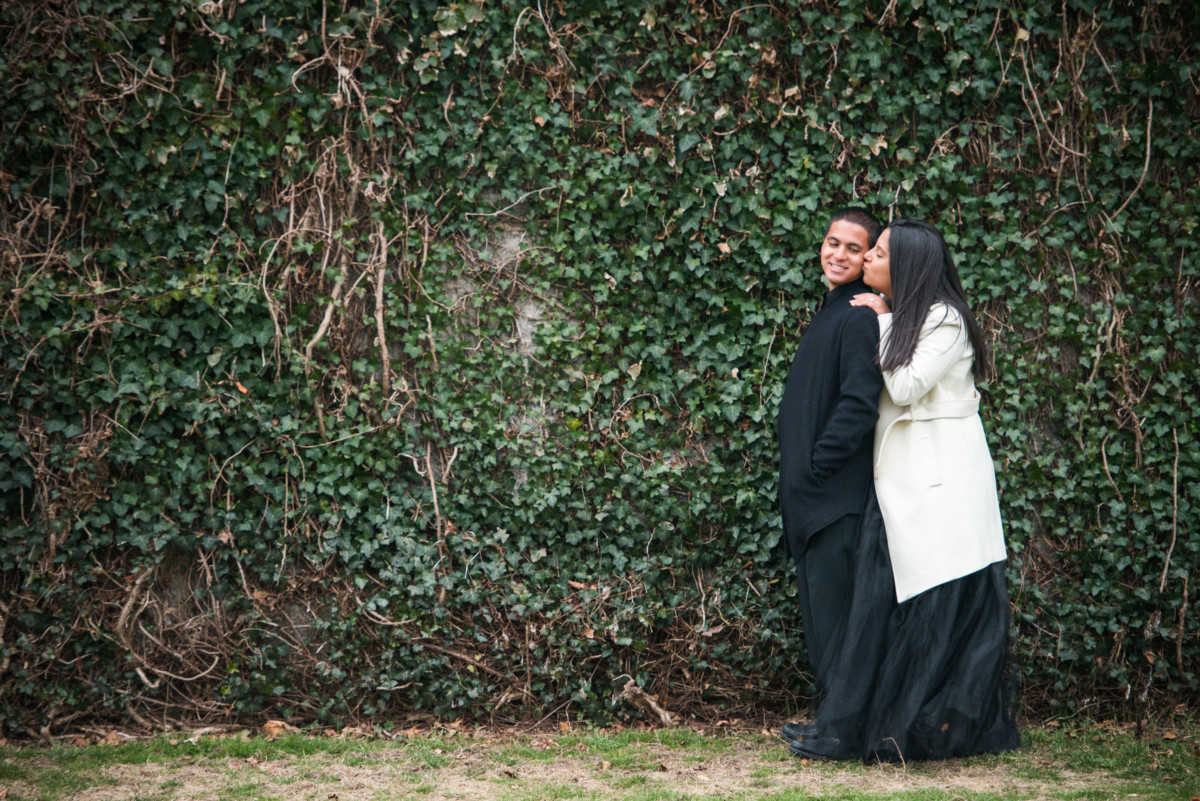 Downtown Providence Engagement - Kiss by ivy covered wall, profile