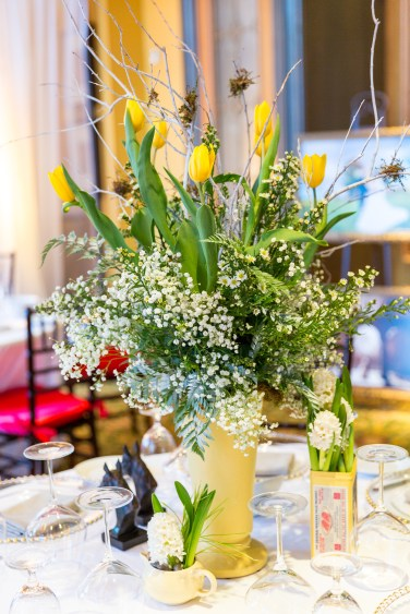 Tulips, whtie branches, moss and babies breath in a vintage vase makes a beautiful centerpiece for a country wedding or event.