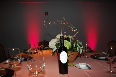 Vineyard theme, bride created table names out of wire. Floral containers were painted to create a wine barrel look.