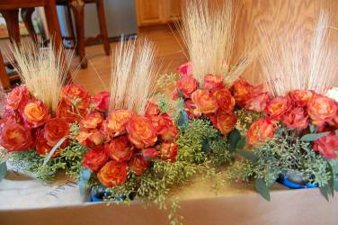 Orange tinted spray roses, wheat and seeded euch.
