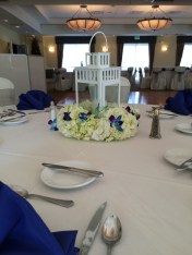 Lantern centerpiece with pillow of white hydrangea and blue orchids