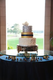 Stunning gold, navy, silver and white wedding cake by Anna Cakes floating on top of gold mercury and gems