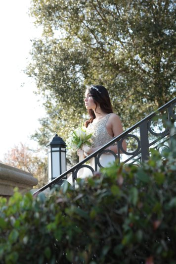 Bride on steps with all white bridal bouquet