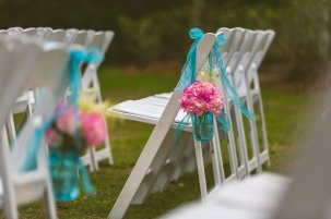 Aisle markers with blue bell jars, bright pink hydrangea and astillbe