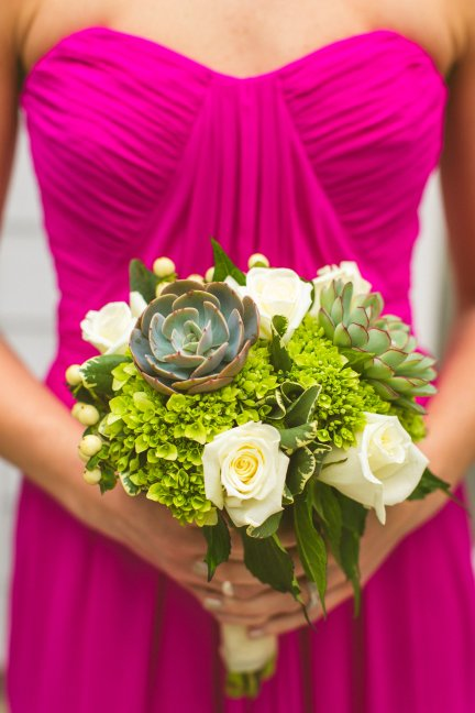 Raspberry bridesmaid with green and white bouquet with succulents