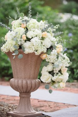As entrance decor into the wedding, we designed romantic overflowing arrangements inside our sandstone urns, filled with White Hydrangea, Peach Standard Roses, Euchs, and Ivory Roses.