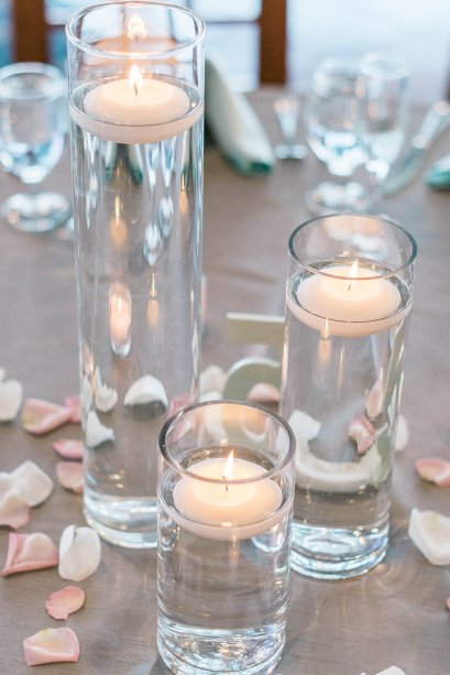 Our elegant clear glass cylinder centerpieces that placed floating candles inside.
