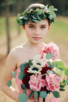 Flower girl with silver dollar halo, carrying bouquets of anemone, burgundy and antique carnations, silver dollar eucalyptus with trailing burgundy velvet ribbons
