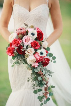 cascading bridal bouquet in red roses, queen protea, white panda anemone, silver dollar euch, pepper berry, scabiosa pods, garden roses and pink roses