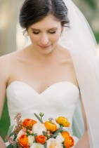 Our bride with her citrus themed bouquet, filled with Orange Ranunculus, Peach Garden Roses, Peach Hypericum Berry, Ivory Standard Roses, and Seeded Euch.
