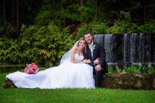 Our Bride and Groom with their tropical floral designs! A bridal bouquet filled with Stargazer Lilies, blue Delphinium, and white Hydrangea & a Groom's boutonniere with a Calla Lily and a blue Delphinium pop.