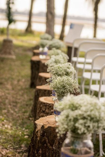 Ceremony setup with Babies Breath filled mason jars on stumps.